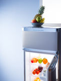 Fruit bowl and open refrigerator Royalty Free Stock Image