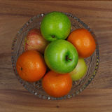 Fruit bowl standing on a wooden table. Crystal vase with apples and oranges on wooden background Stock Photography