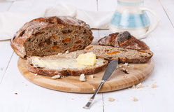 Fruit bread with butter on white wooden background. Fruit bread with butter on a chopping board on white wooden background. Selective focus stock photo