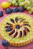 Fruit cake. Delicious fruit cake with grapes peaches and plums stock images