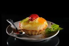 Fruit cake. A fruit cake on white plate whit spoon individualized on black backgound Royalty Free Stock Photo