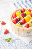 Fruit cake. A fruit birthday cake ,with yellow peach,cherry,kiwi fruit and strawberry on it stock images