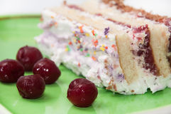 Fruit cake with cherries on green plate with frozen cherries Stock Image