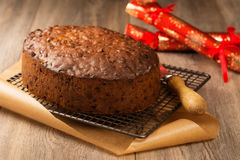 Fruit Cake. Christmas fruit cake ready to ice on cooling rack with crackers in the background royalty free stock photo