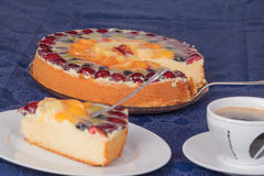 Fruit cake with coffee and cake plate. Fruit cake with coffee and a piece of cake on a plate on blue tablecloth Royalty Free Stock Images