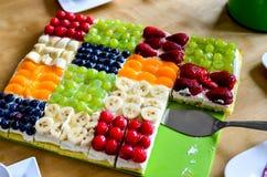 Fruit cake. Colorful fruit sheet cake with cake server stock photos