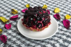 Fruit cake with currant covered with jelly on a saucer on a beau royalty free stock photography