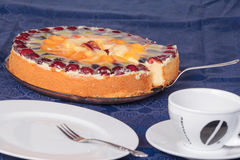 Fruit cake with empty coffee cup and cake plate. Fresh fruit cake with empty coffee cup and cake plate on blue tablecloth Stock Photo