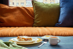 Fruit cake with green tea on the table, beside window and pillows. Daylight, selective focus, film effect Stock Image