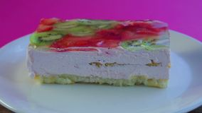 Fruit cake in jelly on a white plate rotates in a circle time laps. Close-up stock video