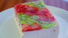Fruit cake with kiwi and strawberries in jelly on a white plate rotates in a circle. Close-up stock video