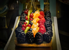 Fruit cake in one pastry shop. In Florence,Italy... with blackberries, currants, kiwi, mandarins ... below the fruits is soft biscuit with vanilla cream stock images