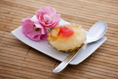 Fruit cake on a plate next to a rose. A delicious fruit cake on a plate with a spoon placed beside two beautiful roses Stock Image