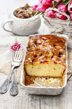 Fruit cake in rectangular pan. Bouquet of pink tulips in the background Royalty Free Stock Images