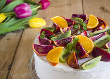 Fruit cake with red oranges. Tangerines, kiwi and mint lying on the wooden table with flowers Royalty Free Stock Images