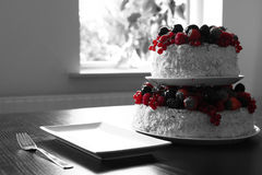 A fruit cake table in black and white with red berries Stock Photos