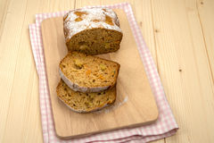 Fruit cake with two pieces on a linen napkin and a light wooden Royalty Free Stock Photos