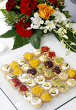 Fruit cakes. On a plateau with flower arrangement on table Stock Photo