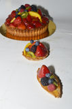 Fruit cakes in different sizes. Small mediam and large  fruit tart cake with custard, strawbery, raspbery, blackbery, blueberry,  kiwi and mango Stock Image