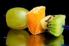 Fruit canape. On toothpick, mirror surface Stock Photo