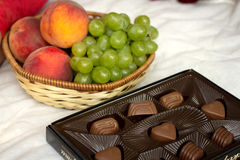 Fruit and candies. Fruit grapes, peaches and chocolates Stock Photo