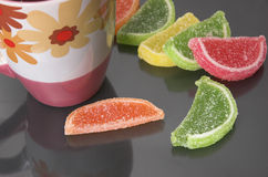 Fruit candy and a mug Royalty Free Stock Image
