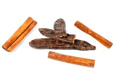 Fruit and carob tree seeds and cinnamon sticks shot close-up on a white background royalty free stock image