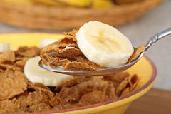 Fruit and cereal. Closeup of a spoonful of wheat flake cereal and banana slice Stock Photos