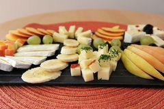 Fruit and cheese platter close-up. Fruit and cheese platter - black plate on a red table mat. Bananas, grapes, pear and peaches with brie and Gouda cheese Royalty Free Stock Photos