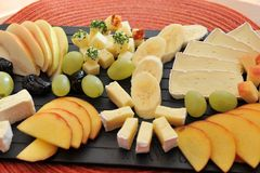 Fruit and cheese platter close-up. Fruit and cheese platter - black plate on a red table mat. Bananas, grapes, pear and peaches with brie and Gouda cheese Royalty Free Stock Photo