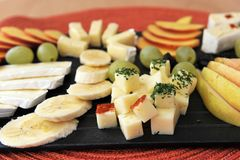 Fruit and cheese platter close-up. Fruit and cheese platter - black plate on a red table mat. Bananas, grapes, pear and peaches with brie and Gouda cheese Royalty Free Stock Images