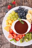 Fruit and chocolate sauce. On wood Royalty Free Stock Photography