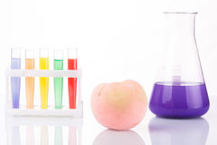 Fruit close chemical test tubes. Genetic. Engineering. pesticides in foods. White background stock photos