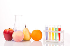 Fruit close chemical test tubes. Genetic. Engineering. pesticides in foods. White background royalty free stock image