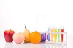 Fruit close chemical test tubes. Genetic. Engineering. pesticides in foods. White background stock image