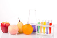 Fruit close chemical test tubes. Genetic. Engineering. pesticides in foods. White background royalty free stock photo