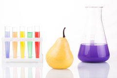Fruit close chemical test tubes. Genetic. Engineering. pesticides in foods. White background stock photo