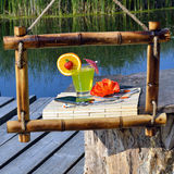 Fruit Cocktail, cell phone, headphones in a bamboo frame on a ba Royalty Free Stock Photos