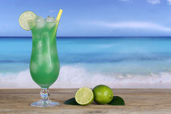 Fruit cocktail with limes on the beach and sea Stock Images