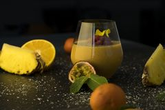 Fruit cocktail smoothie juice in a transparent glass on the table, oranges and tangerines with pineapple and passion stock photos