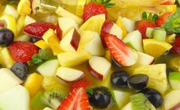 Fruit Cocktail. Zoomed in A Bowl of Fruit Cocktail containing pineapple, strawberry , apple, kiwi fruits, oranges, grapes with orang juice Royalty Free Stock Photos