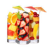 Fruit cocktails isolated on white. Fresh slices of different fruits in glass with mint and umbrellas on the top. Stock Images