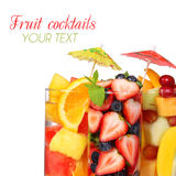 Fruit cocktails isolated on white with space for the text. Fresh slices of different fruits in glass with mint and umbrellas Royalty Free Stock Photo