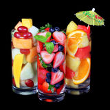 Fruit cocktails over black background. Fresh slices of different fruits in glass with mint and umbrella on the top. Stock Photos