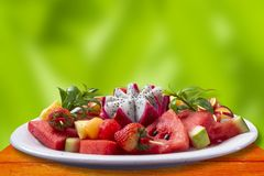 The fruit combineThe fruit combines bright colors with watermelon, strawberry, dragon fruit, pineapple, apples in a white plate, royalty free stock image