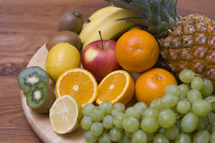 Fruit composition. Some juicy fruit arranged on a wooden board, vivid colours Royalty Free Stock Image