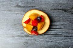Fruit cream roll cake. Slice pastry mango strawberry blackberry Stock Photography