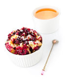 Fruit crumble dessert in a bowl with a cup of tea and teaspoon Stock Photography