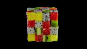 Fruit cube formed from small squares of assorted tropical fruit in a colorful arrangement including kiwifruit, strawberry, orange stock image