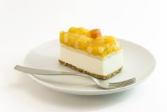 Fruit curd cake on plate. Curd cake with yellow fruits lying on plate stock image